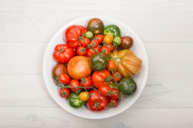 Variété de tomates fraîches dans un bol en bois