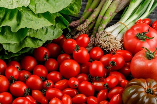 Variété de tomates avec laitue, asperges, gros oignons verts sur un mur en bois