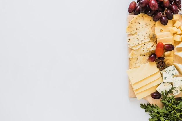 Variété de tranches de fromage et de cubes avec des raisins, tomates et persil sur fond blanc