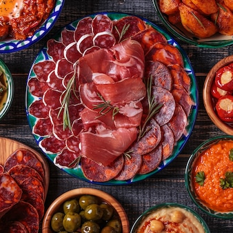 Variété de tranches de jambon, chorizo, salami, bols aux olives, poivrons, anchois, pommes de terre épicées, purée de pois chiches sur une table en bois.