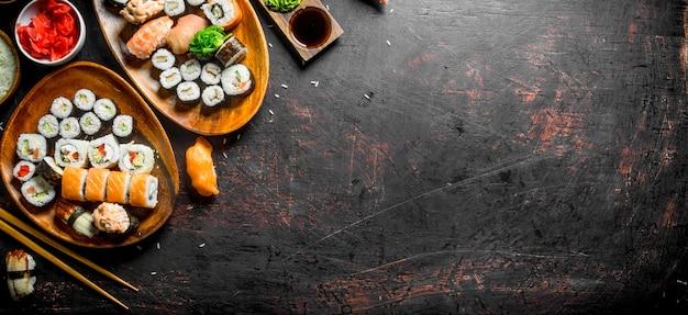 Variété variée de sushis, petits pains et makis dans les assiettes. sur table rustique sombre