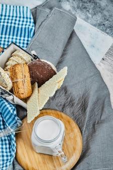 Variétés de biscuits et de craquelins avec un pot de lait.