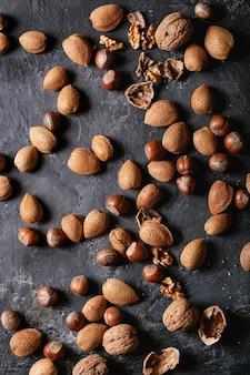 Variétés de noix: amandes, noisettes et noix sur fond de texture sombre