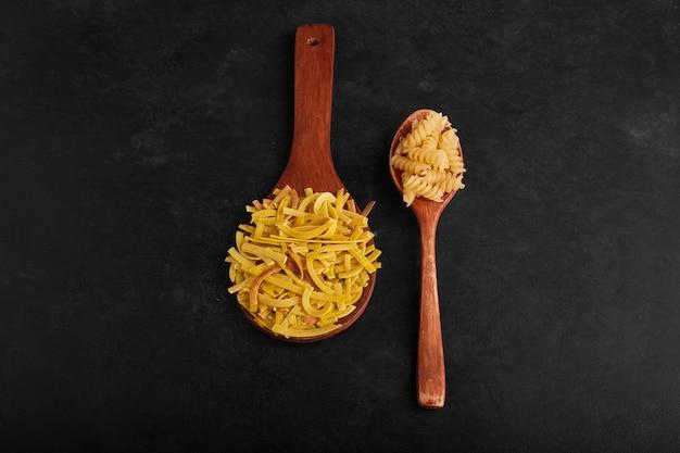 Variétés de pâtes dans des cuillères en bois.