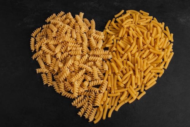 Variétés de pâtes en forme de coeur sur une surface noire.