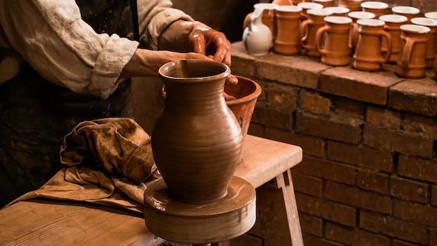 Vase en argile et mains de potier travaillant l'argile