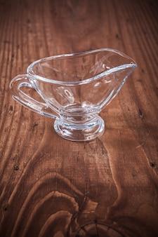 Vase-bateau en verre transparent vide sur une vieille planche de bois