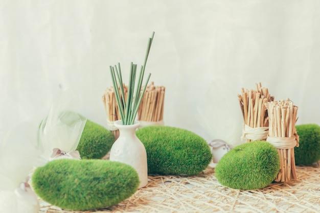 Vase avec des bâtons verts et des pierres moussues