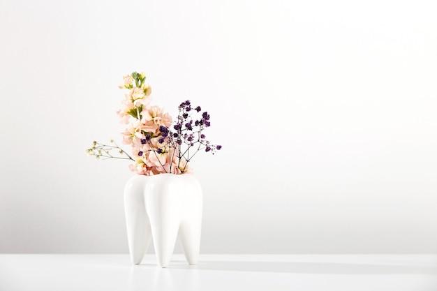 Vase blanc à grosses dents avec des fleurs sur fond blanc et esthétique du dentiste orthodontiste