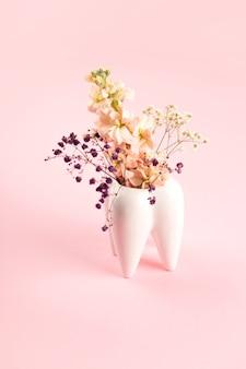 Vase blanc à grosses dents avec des fleurs sur fond rose et esthétique dentiste orthodontiste