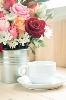 Vase de bouquet roses et tasse de café blanche