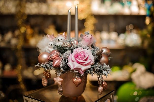 Vase en cuivre avec composition de décoration de noël de branches de sapin, de fleurs roses et de boules