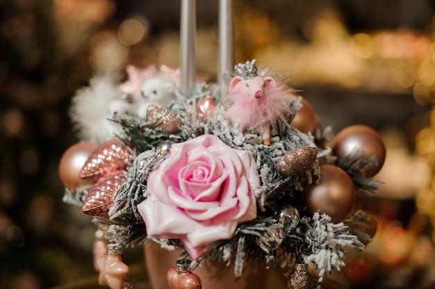 Vase avec décoration de noël composition de branches de sapin, fleur rose et boules de cuivre