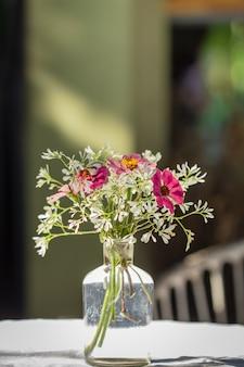 Vase de différents types de fleurs dans la vie en plein air de style vintage