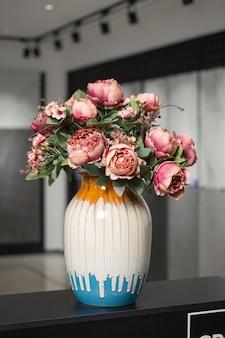 Vase avec des fleurs artificielles roses à l'intérieur.