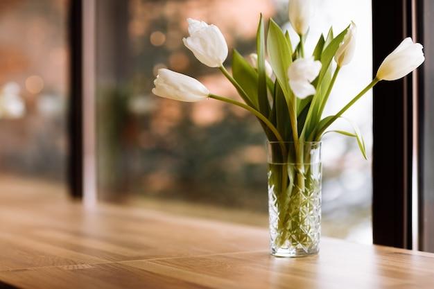 Vase à fleurs blanches sur fond de grandes fenêtres avec table en bois. concept de confort à la maison. bouquet de tulipes dans un vase en verre.