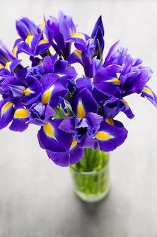 Vase à fleurs iris violet, sur le fond.