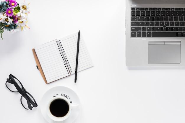 Vase à fleurs; lunettes; journal intime; crayon et tasse à café avec ordinateur portable sur fond blanc