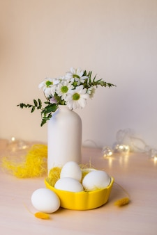 Vase avec des fleurs et des oeufs de pâques avec boken. fond de pâques