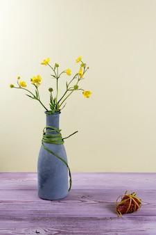 Vase avec des fleurs sauvages et une fraise