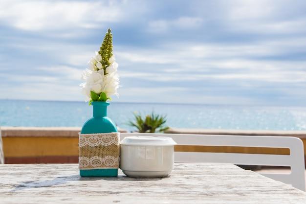 Vase avec les fleurs sur la table dans le café d'été.