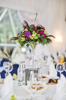 Vase avec des fleurs sur une table ronde servie, dîner dans un restaurant de luxe