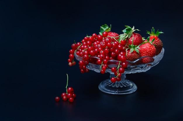 Vase sur une longue jambe avec des fraises rouges et des groseilles rouges sur fond noir. bouquet de baies.