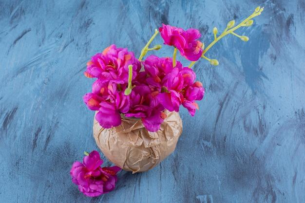 Un vase en papier avec de belles fleurs violettes fraîches sur fond bleu.
