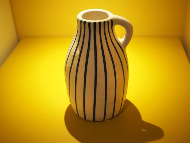 Un vase à rayures dans une boîte remplie de lumière jaune