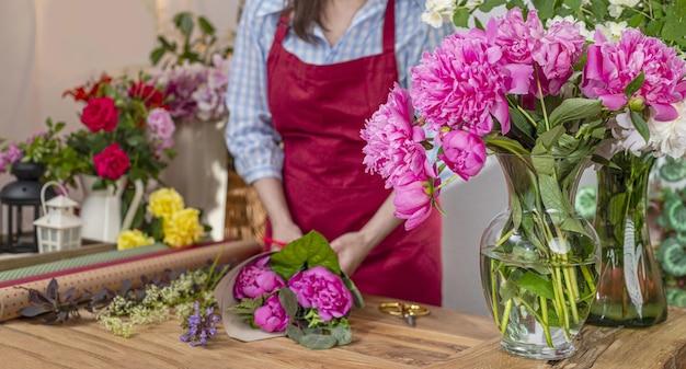 Vase en verre aux pivoines en fleurs, saller de fleurs. entreprise de fleuriste. composition de bouquets.