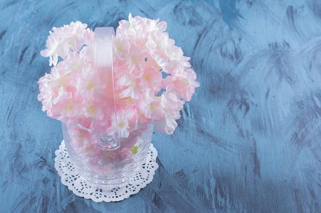 Un vase en verre avec un beau bouquet de fleurs pâles sur fond bleu.