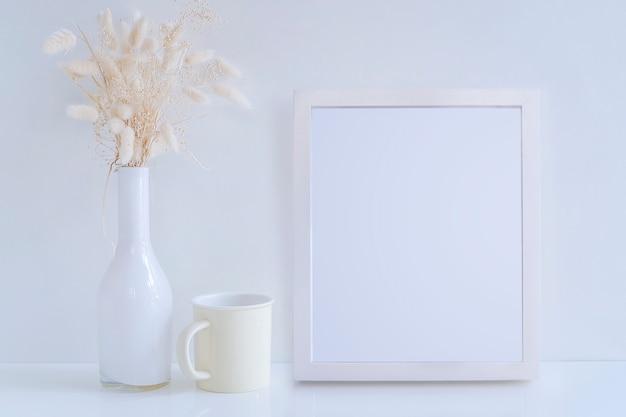 Vase en verre blanc maquette avec fleur de foin et mug jaune sur tableau blanc