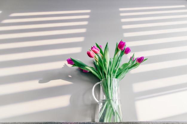 Vase en verre avec bouquet de belles tulipes sur fond de mur gris