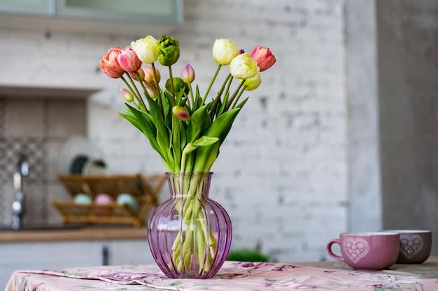 Vase en verre avec bouquet de belles tulipes sur mur de briques