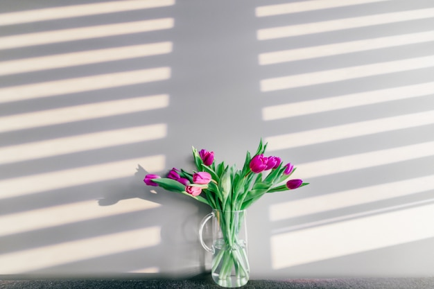 Vase en verre avec bouquet de belles tulipes sur mur gris