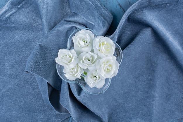 Un vase en verre avec des fleurs artificielles sur nappe.