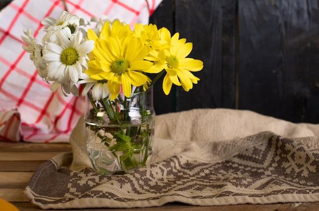 Un vase en verre avec des fleurs jaunes et blanches