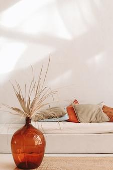 Un vase en verre avec des fleurs séchées debout à côté d'un lit avec différentes couleurs et matériaux naturels