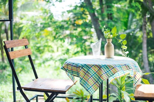 Vase et verre de papier de soie sur table basse fond naturel