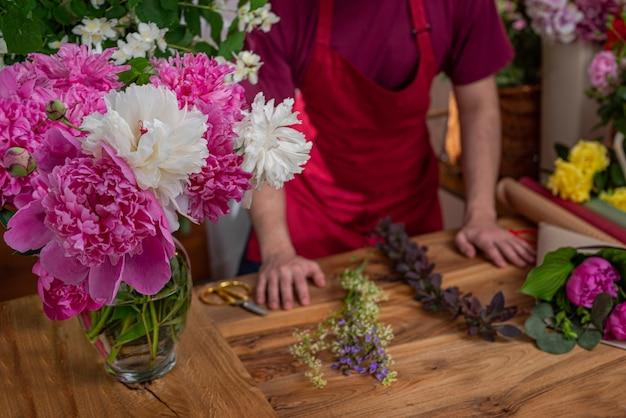 Vase en verre avec des pivoines en fleurs vue sur les cultures vendeur de fleurs entreprise floristique