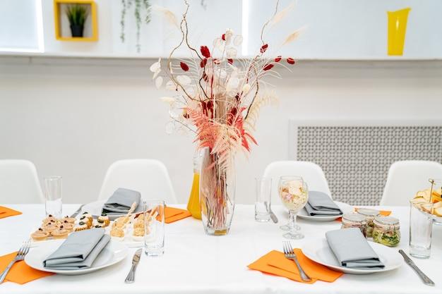 Vase en verre de service de table avec un beau bouquet de fleurs séchées