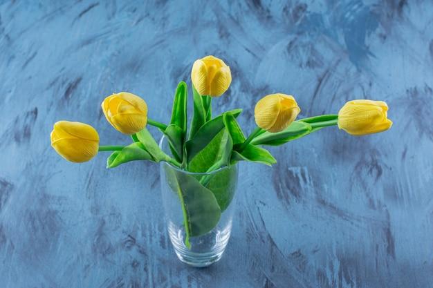 Vase en verre de tulipes jaunes artificielles sur bleu.