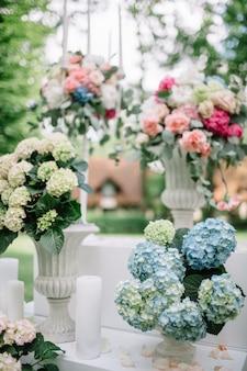 Les vases blancs avec des fleurs se tiennent à l'extérieur