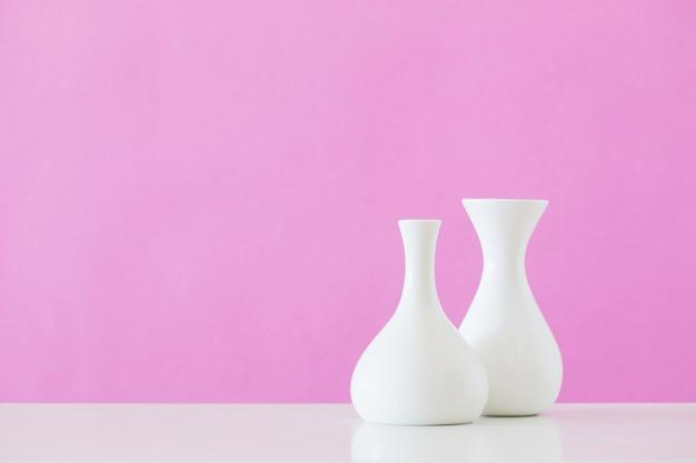 Vases blancs sur mur rose