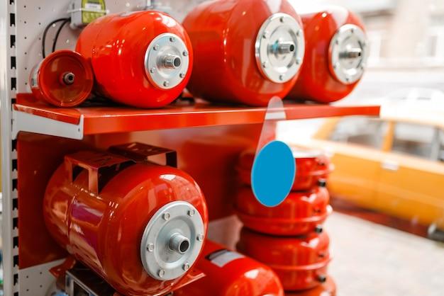 Vases d'expansion pour pompes à eau sur vitrine, magasin de plomberie. atelier d'ingénierie sanitaire professionnel, personne, technologie de plomberie moderne