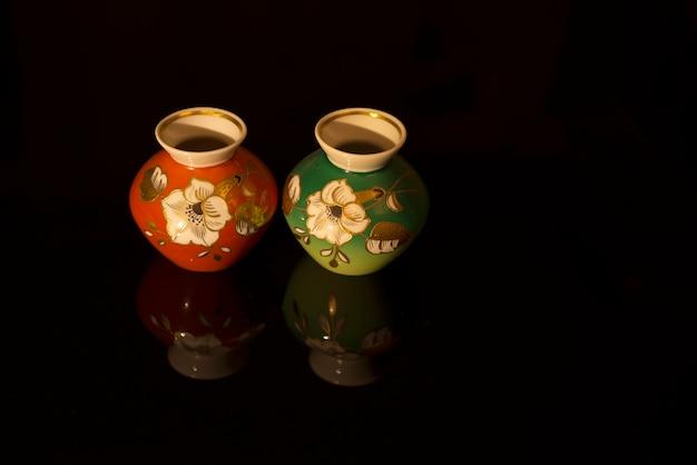 Vases jumeaux, décorés à la main avec des fleurs blanches, placés sur une surface réfléchissante noire