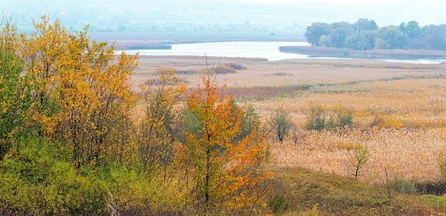 Une vaste plaine avec des arbres et une rivière au loin en automne aux couleurs chaudes