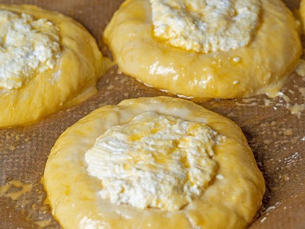Vatrushka étalé sur du papier sulfurisé avant d'être envoyé au four. le concept de gâteaux faits maison