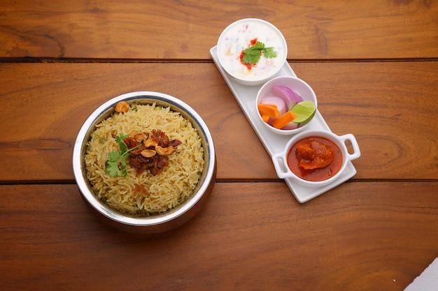 Veg biriyani garni d'oignons frits, de feuilles de coriandre et de noix de cajou dans un récipient en laiton antique