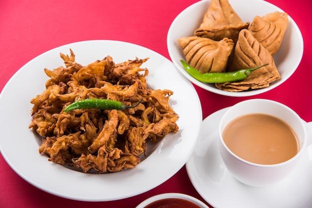 Veg samosa - est une collation indienne croustillante et épicée à l'heure du thé en forme de triangle. servi avec du piment vert frit, de l'oignon et du chutney ou du ketchup. sur fond coloré ou en bois. mise au point sélective